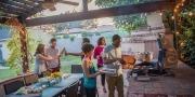 vrienden eten samen onder overkapping in de tuin