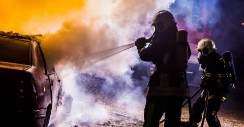 Twee brandweerlieden blussen van een brandende auto met water, schade particulier, verkeer, brand, autobrand, brandweerlieden, blussen, brand blussen