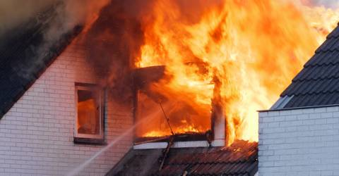 Vlammen uit het raam van een woning